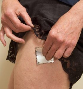 Woman applying a transdermal hormone replacement patch