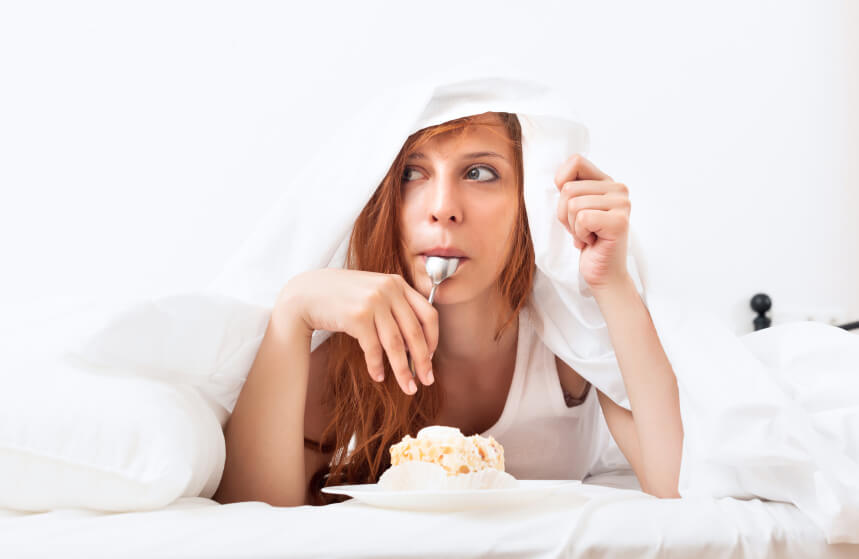 Woman eating dessert on the bed