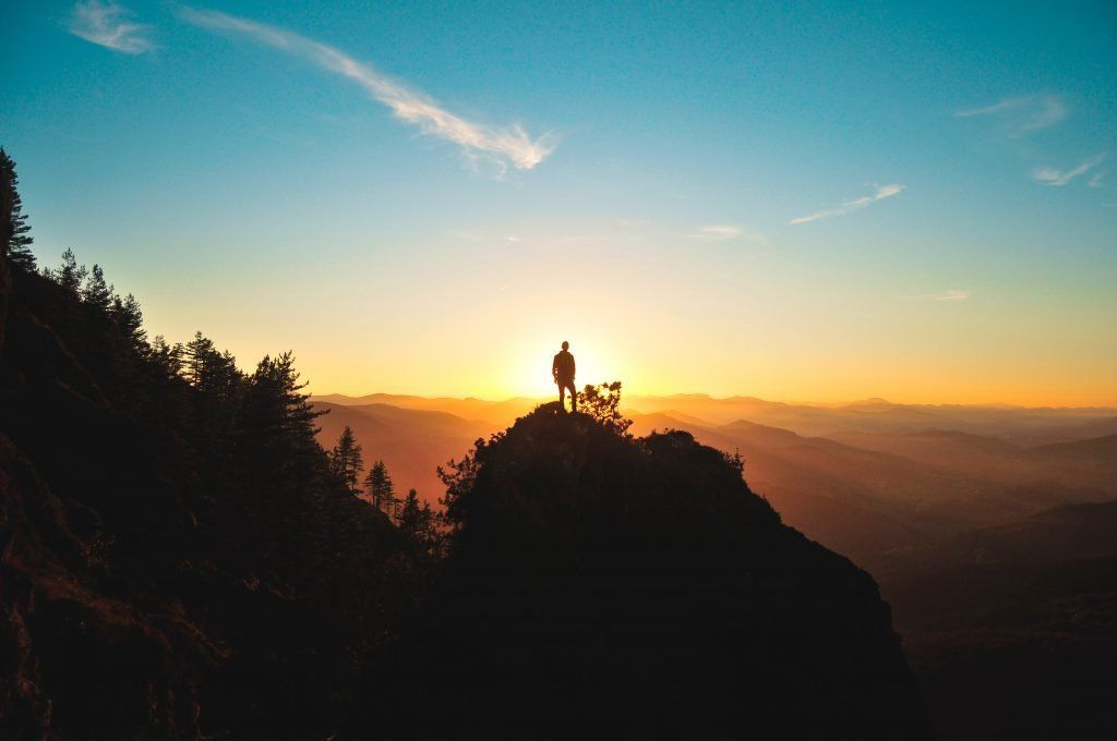 Man watching a sunrise on a mountaintop - Photo by Julentto Photography on Unsplash