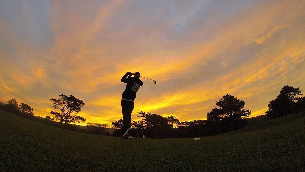 A man tees off into the sunset
