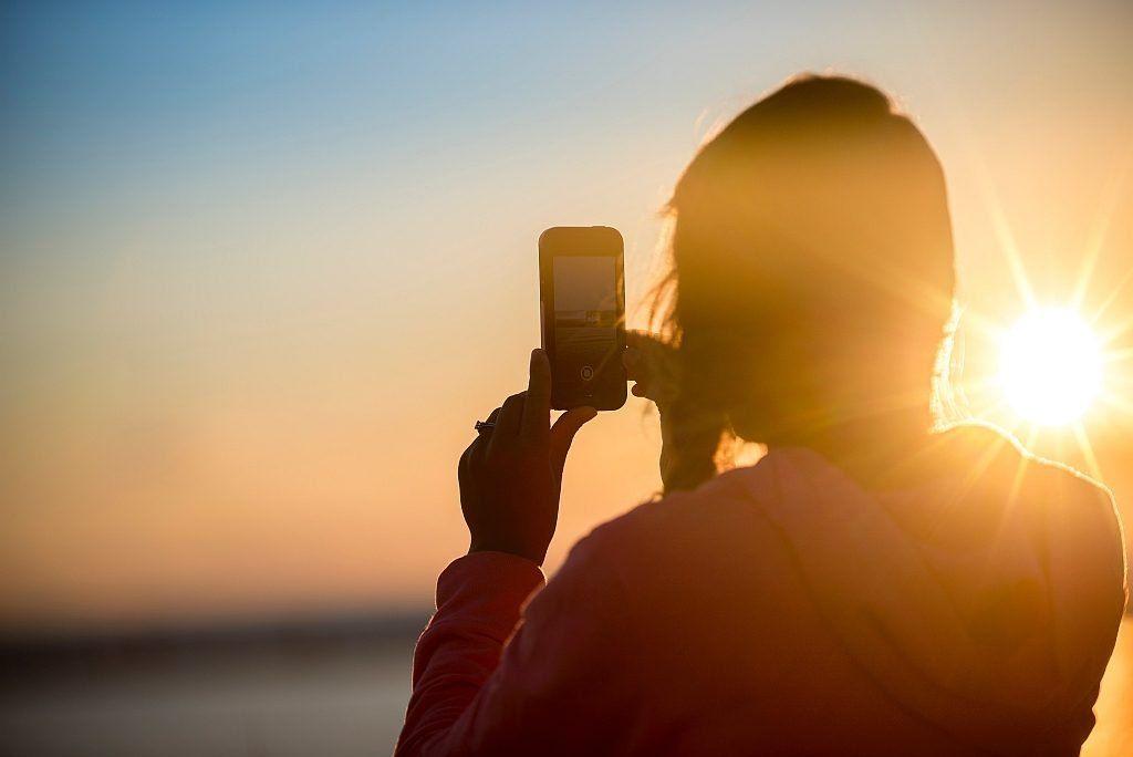 A woman captures a sunset