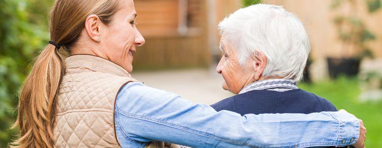 Woman with arm around elderly woman