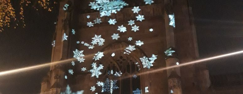light projections of stars across the tower of Derby Cathedral at night