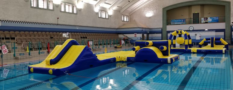 A large blue and yellow inflatable obstacle course with slides and slopes in a swimming pool