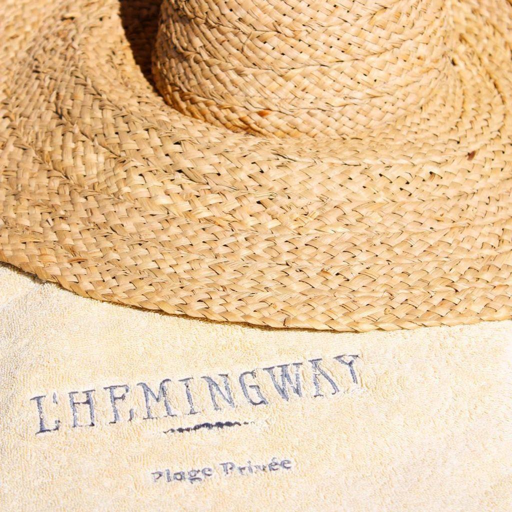Chapeau sur serviette plage privée l'Hemingway