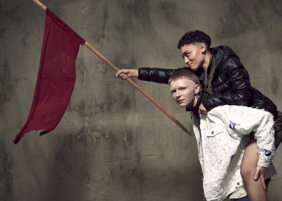 Zwei Menschen mit roter Flagge vor Wand auf der Fashion Revolution Week