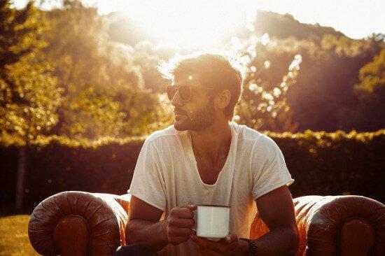 Man auf Sessel mit Kerbholz Sonnenbrille und Becher in der Hand