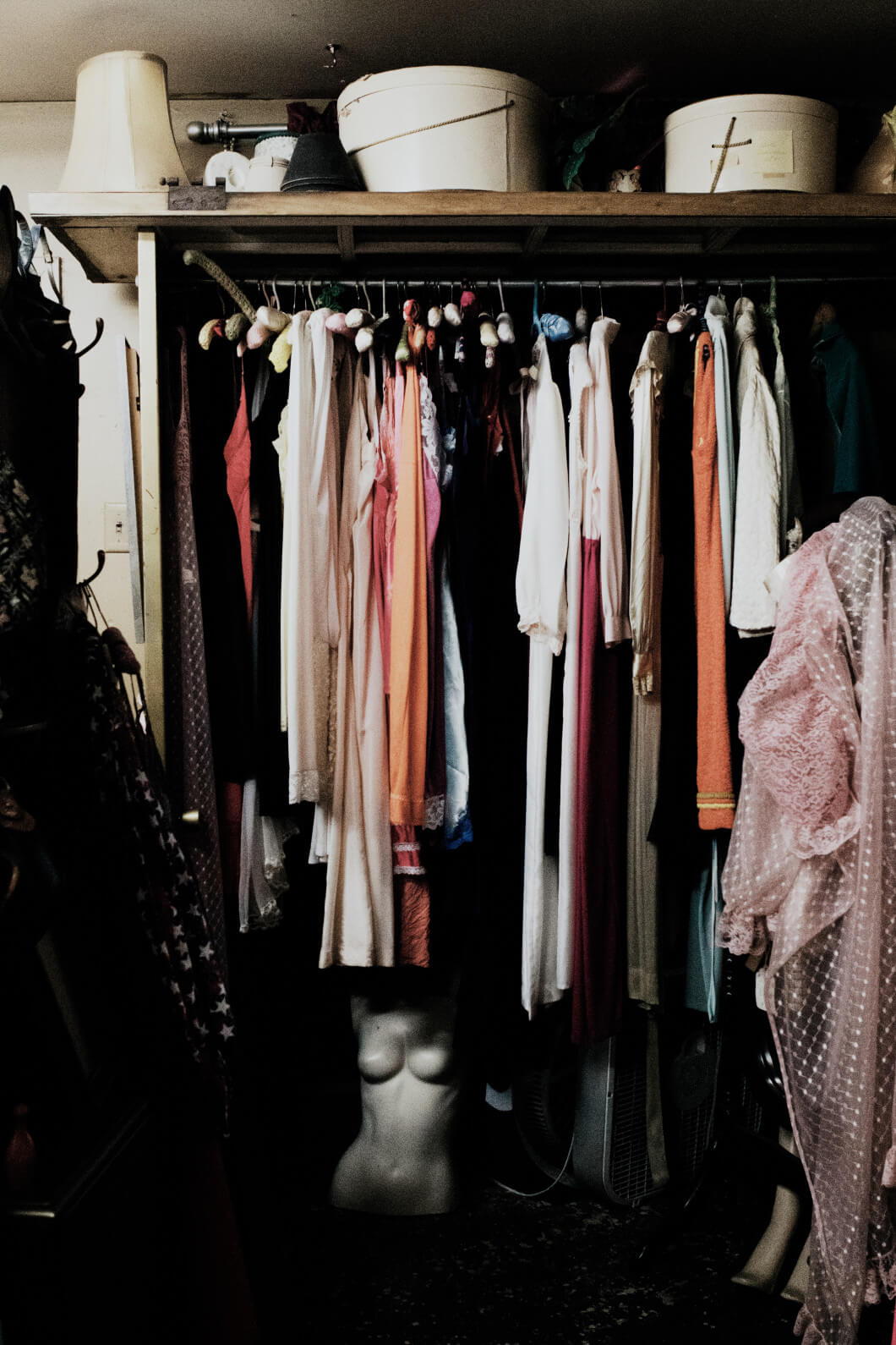 Kleiderschrank mit Kleidung auf Bügeln und Hutschachteln