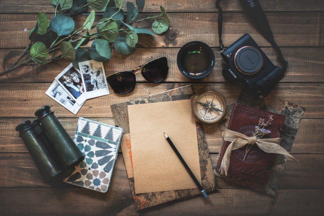 Stillleben auf Holztisch mit Kamera, Papier, Fotos, Sonnenbrille und Fernglas