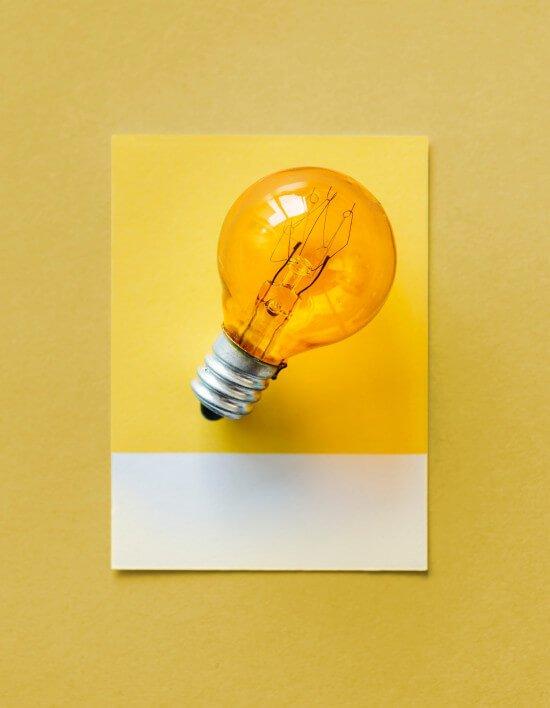 Glühbirne vor gelbem Hintergrund