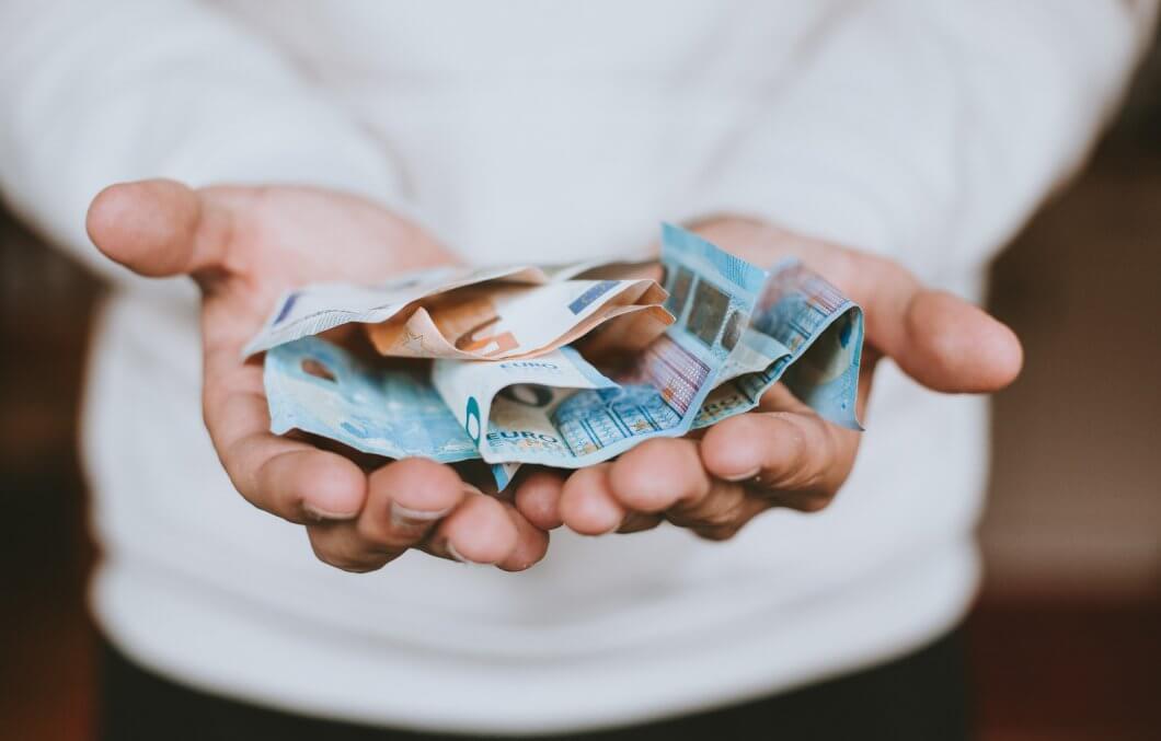 Mann mit Euro-Geldscheinen in den offenen Händen