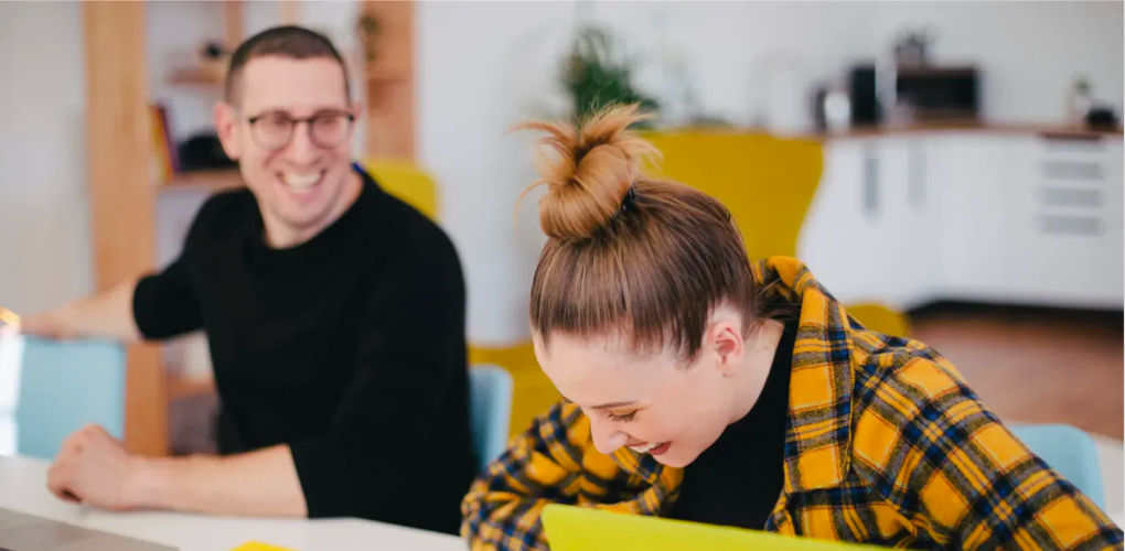 Man and woman sitting and laughing at a desk