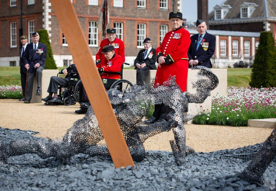 """Normandy veterans pause in the """"D-Day Revisited Garden"""" designed by John Everiss Design, at the RHS Chelsea Flower Show during press day in London, May 20, 2019. Photograph by Suzanne Plunkett/RHS"""