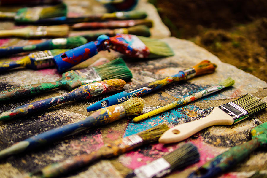 Paint brushes covered in various paints