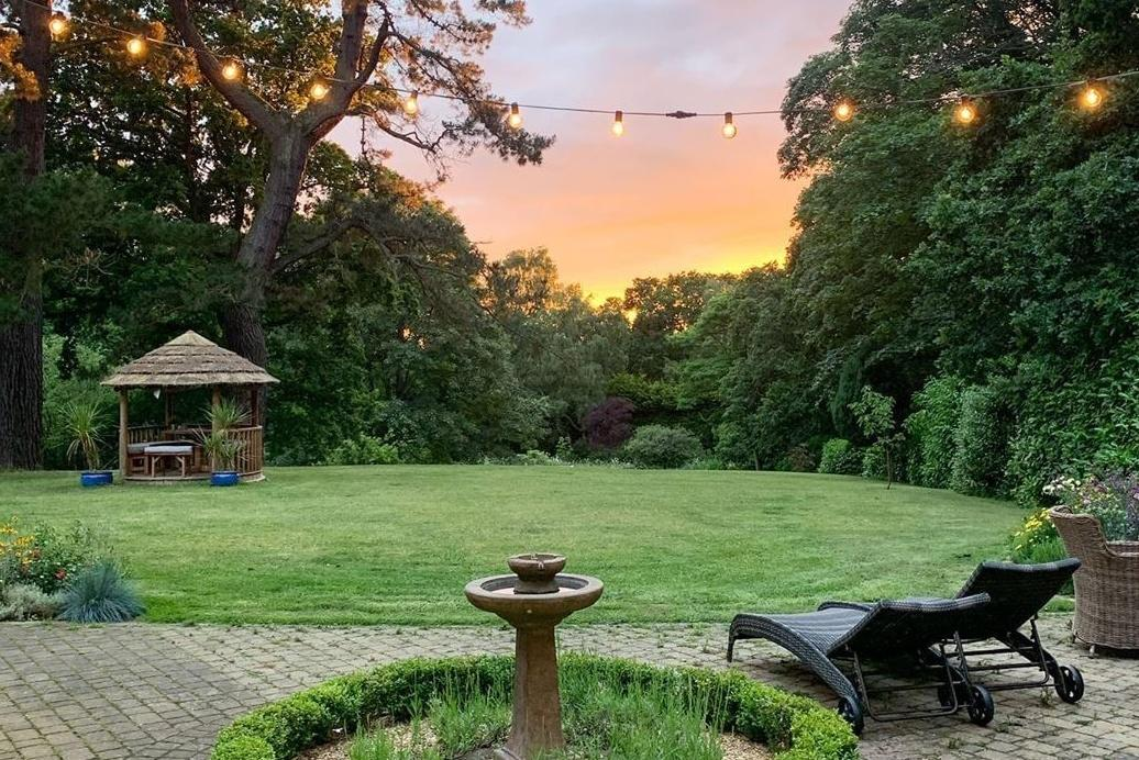 Garden at sunset with two sun loungers and a Breeze House garden gazebo in the background