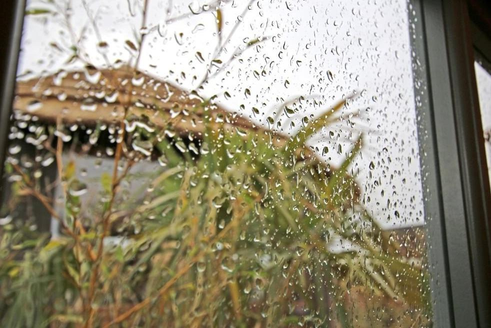 Rain on window on garden studio with view on breeze house thatched roof