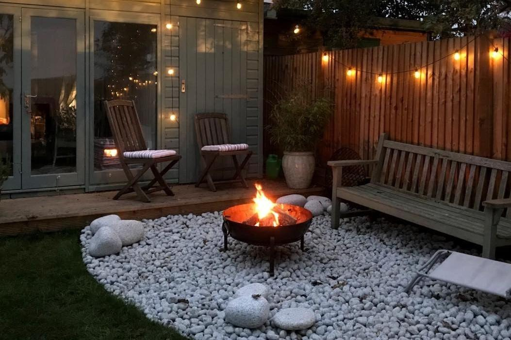 Early evening in garden with lit firepit and festoon lights decorating garden studio