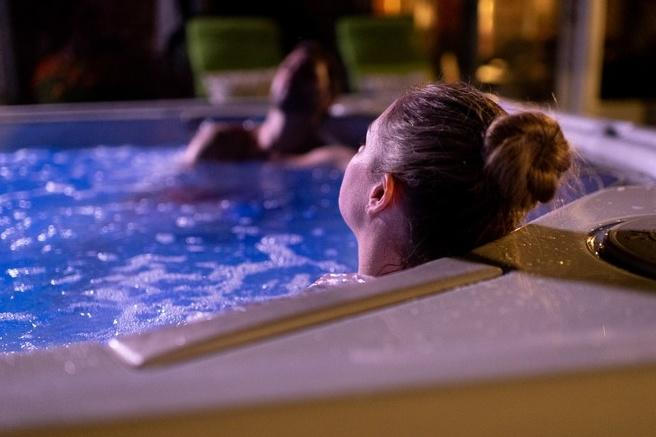 Couple reposing in a hydrofoil hot tub at night