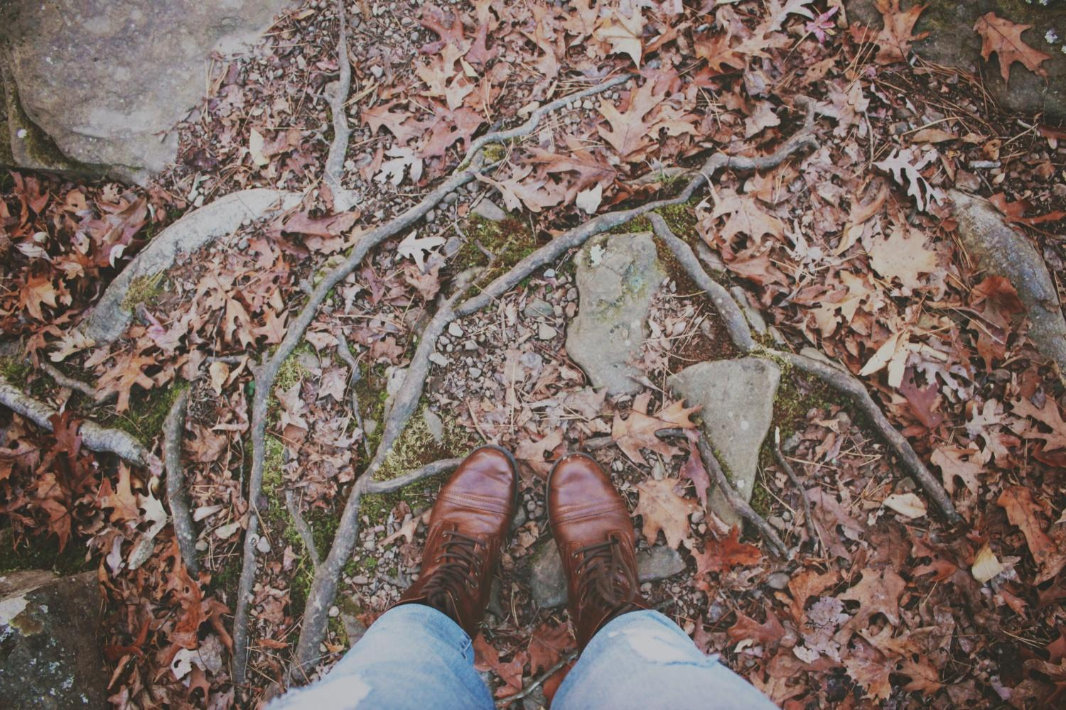 Looking down at boots while standing in forest covered with autumn leaves