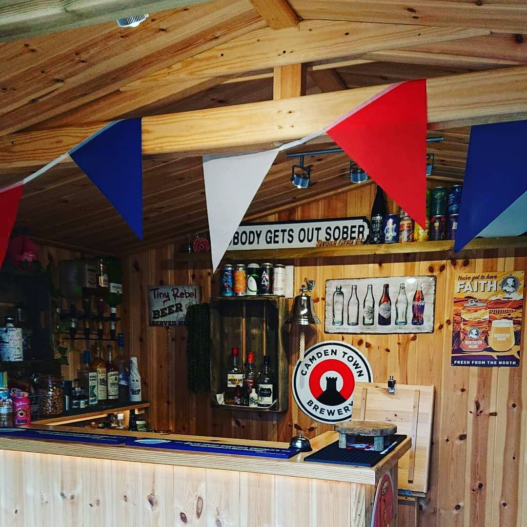 """The interior of a wooden garden building that has red, white and blue bunting strung up. There is a wooden bar stocked with beers and spirits. On the wall there is a sign that says """"nobody gets out sober""""."""