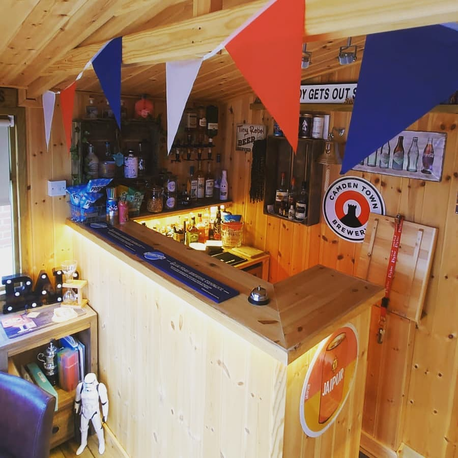 The interior of a wooden garden building that has a wooden bar stocked with beers and spirits.
