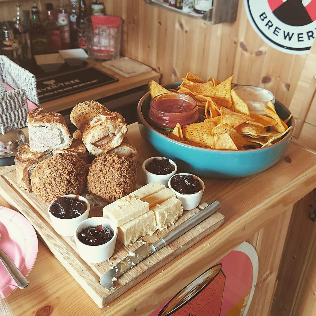 A food platter of pastries, scotch eggs, cheese, chutney, crisps and dips