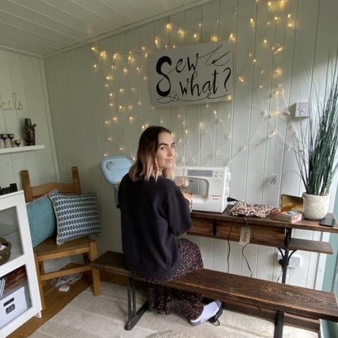 Young m=woman sat at sewing machine in garden studio
