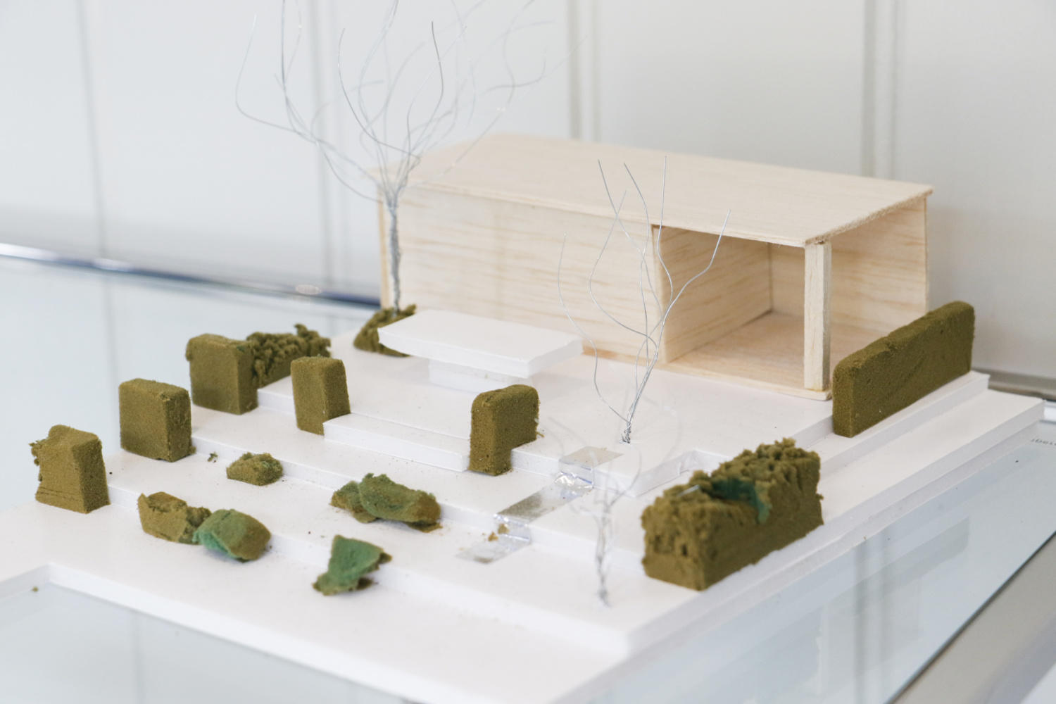 Close up of a model made out of wood, paper, wire and polystyrene on a garden design