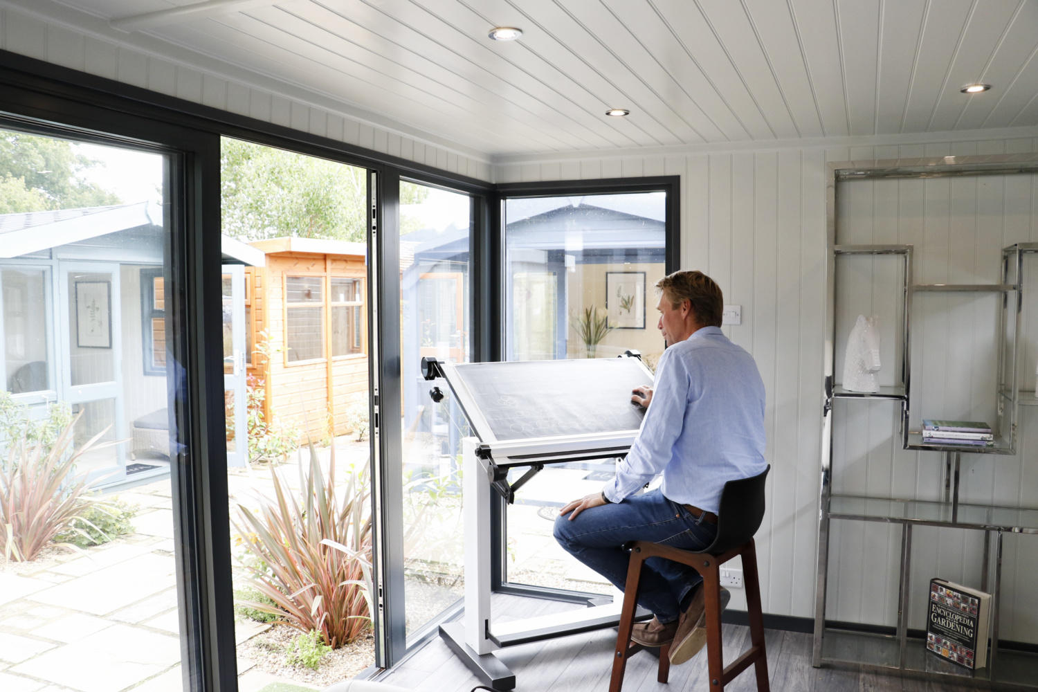 Tom Gadsby sits in the window of a garden office, next to his architects table with drawings and plans of a new garden