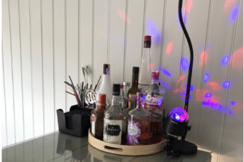 A collection of alcoholic spirits sit atop a bar, next to multicoloured disco lights that dance up the wall