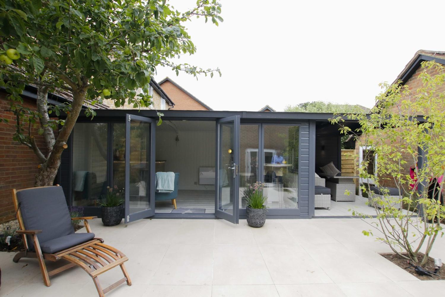 A wide garden building sits at the top of a pated garden, with the doors open wide. A modern version of The Pleasure Garden