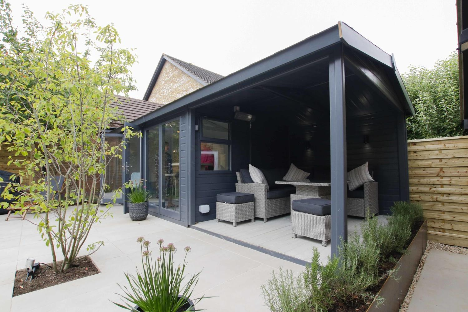 A garden building with an open sided area with comfortable lounge seating, surrounded by tidy planting