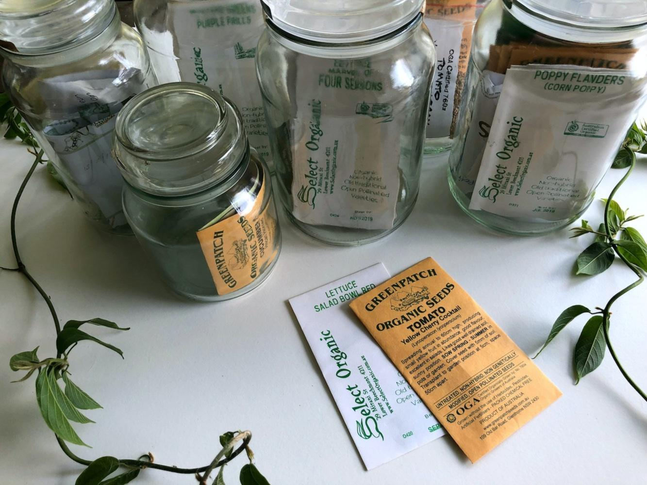 A collection of glass jars filled with vintage-looking paper seed packets. Two packets are out of the jars, one reads 'Greenpatch Organc Seeds Tomato' and the other reads 'Select Organic Lettuce Salad Bowl Red. Be inspired to grow your own in a victory garden at home.
