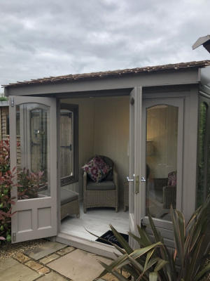 A small light grey rectangular summerhouse. The windows are full length and the double doors are open to show the cosy interior.