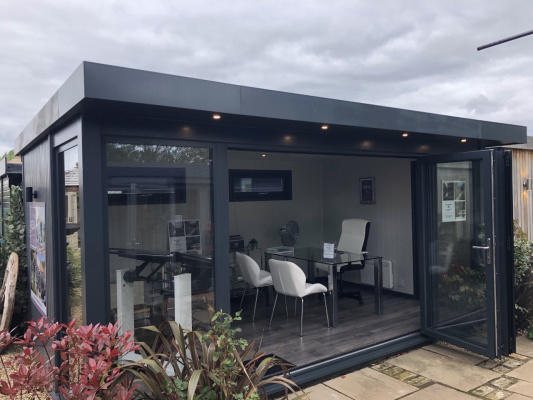 A large, metallic dark grey rectangular garden building. The doors are open to show a modern office area inside.