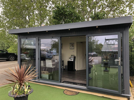 A large rectangular garden building in graphite grey with full length glass windows and doors. The doors are open to show a modern interior.