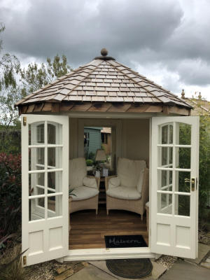 A small, white square summerhouse with Georgian windows and double doors. The roof is hipped and made of cedar shingles. The double doors are open to reveal a cosy interior