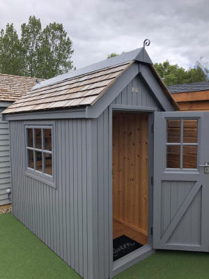 A small, blue-grey wooden shed with a pointed shingle roof. It has one medium window to the side and a single door with a glass pane. The door is open to show the interior.