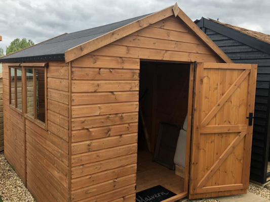 A large redwood shed with a pointed roof, a side window and an open front door.