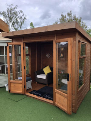 A small, square redwood summerhouse with large windows and double doors. The doors are open to show the interior.