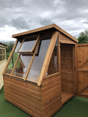 A small redwood shed with a large glass skylight.
