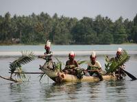 Locals in een van de typische fluisterboten op het water. © Heritage Expeditions