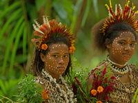 Twee lokale meisjes zijn versierd voor een van de jaarlijkse festiviteiten in het dorp. © Heritage Expeditions
