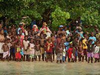 Het Iwa volk samen met enkele deelnemers op het strand voor het dorp. © Heritage Expeditions