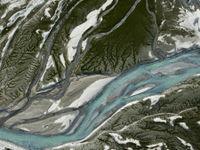 Een luchtfoto van azuurblauw smeltwater dat over het zand en de kiezels aan de voet van een gletsjer stroomt. © Sebastian Vervenne