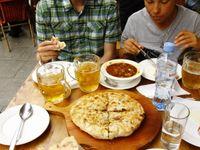 Traditionele maaltijd in Svaneti, met kubdauri, een soort 'calzone'-pizza gevuld met kruidig gehakt. © Johannes Jansen