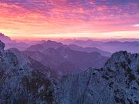 Mistige bergtoppen bij een ondergaande zon. © Bart Heirweg