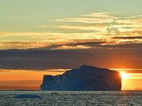 Een gigantische ijsberg met de ondergaande zon op de achtergrond. © Yves Adams
