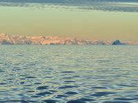 Een verre kustlijn met op de voorgrond het water van de Noordelijke IJszee. © Yves Adams