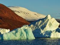 Een laagstaande zon kleurt het landschap geel boven de toendravlaktes van Groenland. © Yves Adams